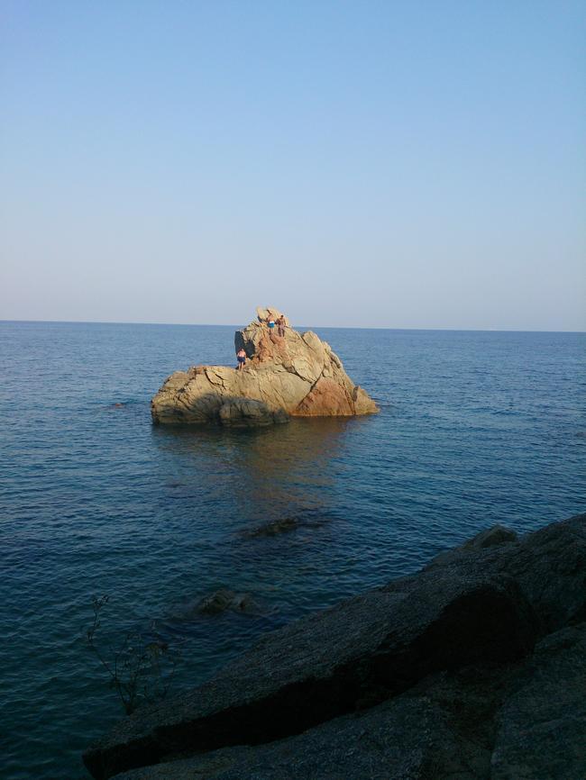 мальчишки прыгают с камней в море
