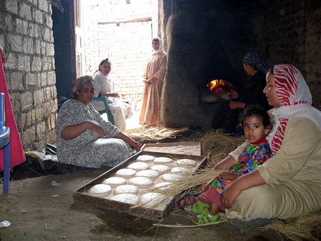Женщины пекут хлеб. Самая опытная сидит у печи, а остальные по о